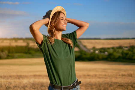 Woman farmer straw hat standing farmland smiling Female agronomist specialist farming agribusiness Happy positive caucasian worker agricultural field Pretty girl denim jeans green t-shirt harvest