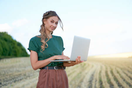 Woman farmer smart farming standing farmland smiling using laptop Female agronomist specialist research monitoring analysis data agribusiness Caucasian worker agricultural field 스톡 콘텐츠 - 165320744