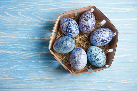 Blue chicken eggs lie in round wooden basket which stands on a blue wooden table. Easter background. Seasonal holiday flat lay with free space for text. Classic blue color of the year 2020 스톡 콘텐츠