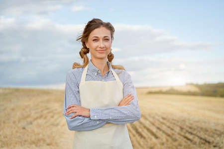 Woman farmer apron standing farmland smiling Female agronomist specialist farming agribusiness Happy positive caucasian worker agricultural field Pretty girl arms crossed cloudy sky background 스톡 콘텐츠