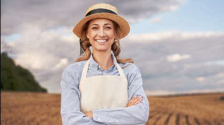 Woman farmer straw hat apron standing farmland smiling Female agronomist specialist farming agribusiness Happy positive caucasian worker agricultural field Girl arms crossed cloudy sky background