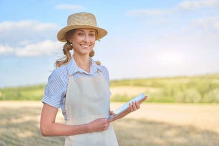Woman farmer straw hat smart farming standing farmland smiling using digital tablet Female agronomist specialist research monitoring analysis data agribusiness Caucasian worker agricultural field