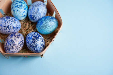 Blue chicken eggs lie in round wooden basket which stands on a blue paper background. Easter background. Seasonal holiday flat lay with free space for text. Classic blue color of the year 2020