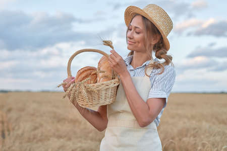 Female farmer standing wheat agricultural field Woman baker holding wicker basket bread eco product Baking small business Caucasian person dressed straw hat apron organic healthy food concept