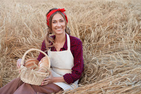 Female farmer sitting wheat agricultural field Woman baker holding wicker basket bread eco product Baking small business Caucasian person dressed red plaid shirt apron organic healthy food 스톡 콘텐츠