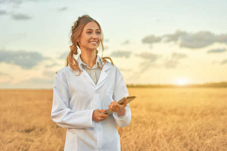 Woman farmer white coat smart farming standing farmland smiling using digital tablet Female agronomist specialist research monitoring analysis data agribusiness Caucasian worker agricultural field