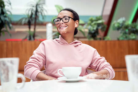 Black african american woman with vitiligo pigmentation skin problem indoor dressed pink hoodie glasses sitiing table indoor drink tea 스톡 콘텐츠 - 165811758