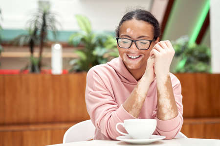 Black african american woman with vitiligo pigmentation skin problem indoor dressed pink hoodie glasses sitiing table indoor drink tea smiling Happy positive person waiting in restaurant