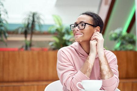Black african american woman with vitiligo pigmentation skin problem indoor dressed pink hoodie glasses sitiing table indoor drink tea