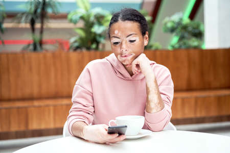 Black african american woman with vitiligo pigmentation skin problem indoor dressed pink hoodie sitting table using smartphone Banque d'images