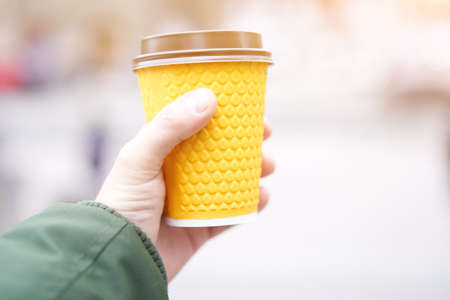 unrecognizable man holding yellow paper cup with coffee in hand on blured street background