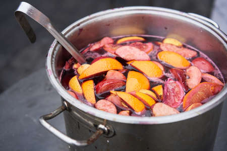closeup of mulled wine, preparing in big old metal kettle on fire, above view, Traditional Christmas fair market beverage 스톡 콘텐츠