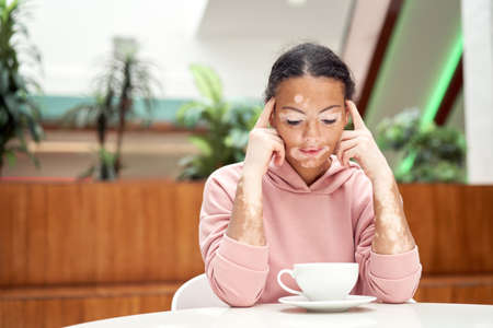 Black african american woman with vitiligo pigmentation skin problem indoor dressed pink hoodie sitting on the table drink tea white cap thinking Drweaming female