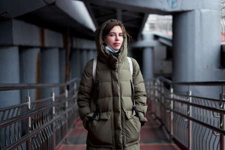 Woman portrait confidence brunette dressed warm winter jacket dark background dramatic atmosphere Caucasian female headshoot Women's parka 스톡 콘텐츠