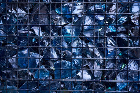 Blue Crystal Mineral Stone. Gems. Artificial crystals in stone cage modern construction wall background Texture of precious and semiprecious stones. colored shiny surface of precious stones