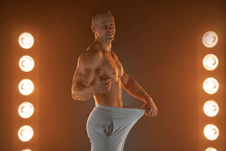 Great male size. Young muscular guy pulling back his pants and showing thumb up gesture, being proud and satisfied with his genitals, lamps illumination on background Weight loss concept Diet Banque d'images