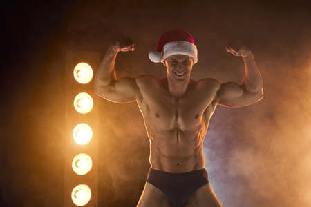 Portrait of muscular man wearing Christmas Santa hat, showing biceps muscle on smoky background Macho Shirtless Naked torso stripper Hot sexy Santa guy Seductive male for holiday