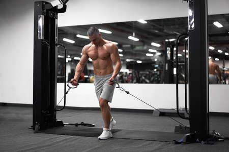 Muscular athletic bodybuilder standing training chest and shoulders muscles on fitness equipment wire cable machine Sport fitness healthy lifestyle Man do flyes exercises on gym machine