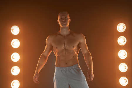 Active lifestyle concept. Professional bodybuilder showing perfect muscular body smiling at camera, lamps illumination smoke on background