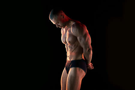 Active lifestyle concept. Professional bodybuilder showing perfect muscular body, lamps illumination on background Sport and fitness concept