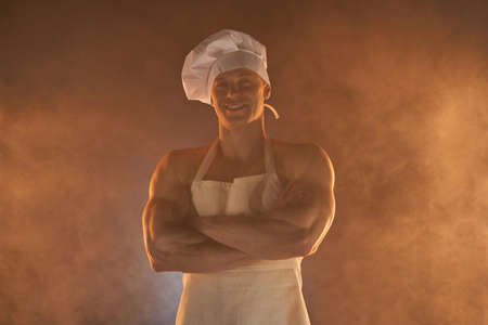 Portrait of muscular chef wearing white apron and chef hat, posing with folded arms on smoky background male housewife. husband in kitchen. brutal butcher.