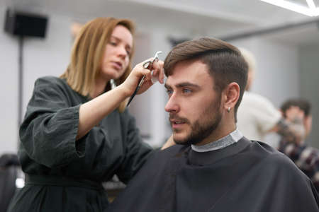 Stylish man sitting barber shop Hairstylist Hairdresser Woman cutting his hair Portrait handsome happy young bearded caucasian guy getting trendy haircut Attractive barber girl working serving client Banque d'images