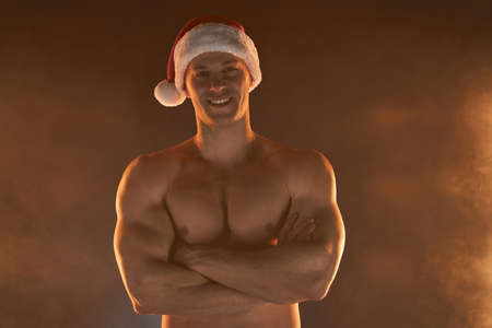 Portrait of muscular man wearing Christmas Santa hat, folded hands and smile on smoky background Macho Shirtless Naked torso stripper Hot sexy Santa guy Seductive male for holiday