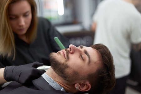 Young adult beautiful caucasian woman hairdresser cuts beard handsome man at modern barbershop Happy gay sitting chair men beauty salon. beard care. metrosexual. Female barber in black gloves serving