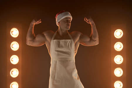 Hot Christmas dessert Sexy muscular Chef wearing apron and Santa hat show biceps smiling, lamps illumination and smoke on background cuisine. male housewife. husband in kitchen. brutal butcher. Banque d'images