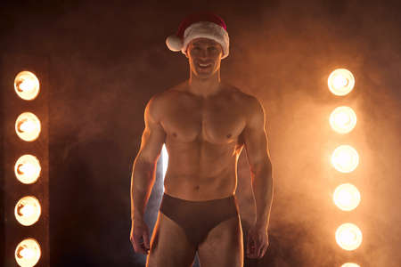 Portrait of muscular man wearing Christmas Santa hat, standing athletic pose on smoky background Macho Shirtless Naked torso stripper Hot sexy Santa guy Seductive male for holiday