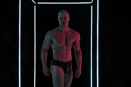 Active lifestyle concept. Professional bodybuilder showing perfect muscular body, neon lamps illumination on background Sport and fitness concept Banque d'images