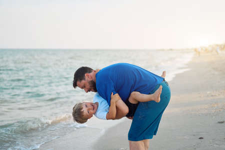 Father son spending time together sea vacation Young dad child little boy walking beach Fathers day. Family with one child. Happy childhood with daddy. sitting on hands laughs Banque d'images