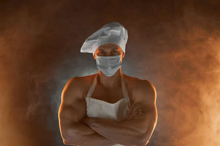 New normal concept. Portrait of muscular chef wearing protective medical mask white apron and chef hat, posing with folded arms on smoky background male housewife. husband in kitchen. brutal butcher.