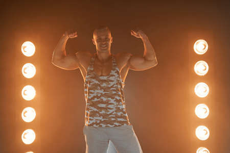 Active lifestyle concept. Professional bodybuilder showing biceps and smiling at camera, lamps illumination and smoke on background