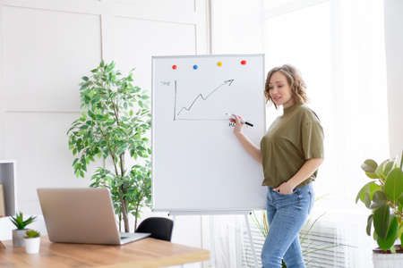 Online presentation, webinar, online meeting. Young business woman speaks to the audience video call, video connection. She stands near flip chart and looks at screen with online viewers Banque d'images