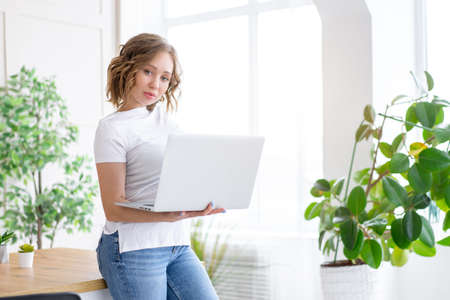 Business woman using laptop standing near desk white office interior with houseplant looking at camera Business people Business person Online, Young and successful Dresed white shirt and jeans