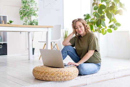 Woman using laptop computer while sitting floor at home interior. Freelance female working from home Distance learning student relaxing and watch
