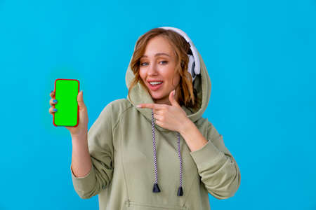 Woman listen music headphones holding smartphone in hand looking camera showing finger device screen Caucasian female enjoy podcast or audio books dressed oversize hoodie blue background advertising