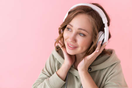 Happy teeth smile woman listen music headphones Caucasian female enjoy podcast or audio books dressed oversize hoodie pink background close up portrait Banque d'images