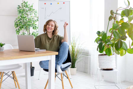 Business woman using laptop sitting desk white office interior with houseplant looking Business people Business person Online, Young and successful Dresed green shirt blue jeans barefoot relaxing Banque d'images