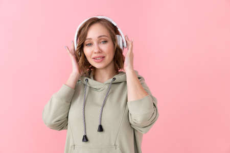 Confident woman listen music headphones Caucasian female enjoy podcast or audio books dressed oversize hoodie pink background close up portrait