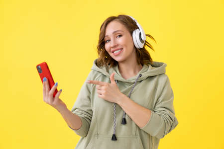 Happy teeth smile woman listen music headphones holding smartphone in hand looking screen Caucasian female enjoy podcast or audio books dressed oversize hoodie yellow background close up portrait Banque d'images