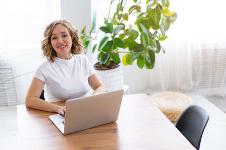 Business woman using laptop sitting near desk white office interior with houseplant looking at camera Business people Business person Online, Young and successful Dresed white shirt