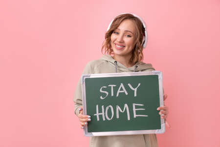 Stay home concept Positive message Woman with headphones dressed oversize hoodie holds chalkboard with the words stay home.  protection New normal concept  pandemic Social distancing