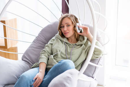 Happy teeth smile woman listen music headphones Caucasian female enjoy podcast or audio books while resting in loft design chair Dressed blue jeans and oversize hoodie