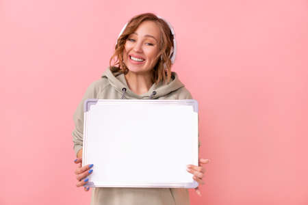 Woman holding empty blank board over pink background Happy Caucasian female 30 years old dressed headphones oversize hoodie hold blank white board sign Studio shoot Advertising Promoting Presentation