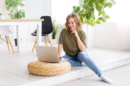 Woman using laptop computer while sitting floor at home interior. Freelance female working from home Distance learning student relaxing and watch lessons on video conference