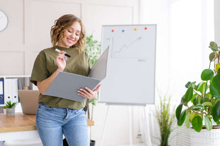 Businesswoman holding folder for paper write marker thinking dreaming standing near office table. Business person femal ypoung adult caucasian on modern white interior