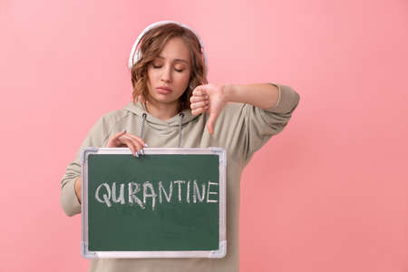 Stay home concept Woman with headphones dressed oversize hoodie holds chalkboard with the words quarantine.  protection New normal concept  pandemic Social distancing work from home Banque d'images