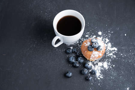 Blueberry antioxidant organic superfood and sweet muffin with cup of coffe Concept for healthy eating and dieting nutrition Top view on dark black background